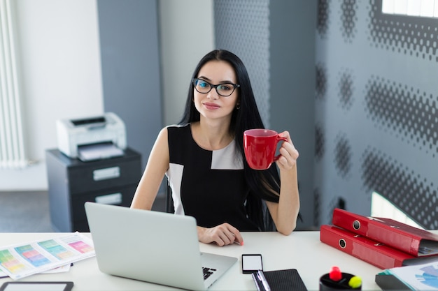 Beautiful young businesswoman in black dress and glasses sit at the table and work with coffe in hand