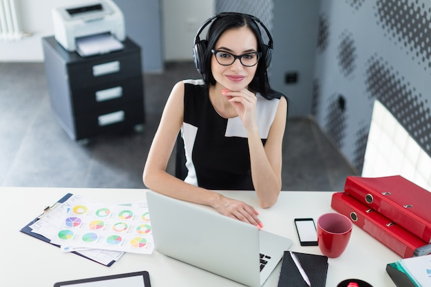 Beautiful young businesswoman in black dress, headphones and glasses sit at the table and work on laptop