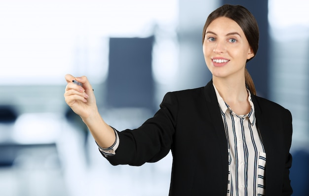 Beautiful young businesswoman pointing at copy space isolated