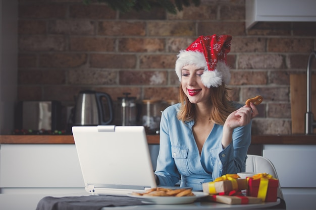 Beautiful young businesswoman in santa claus hat