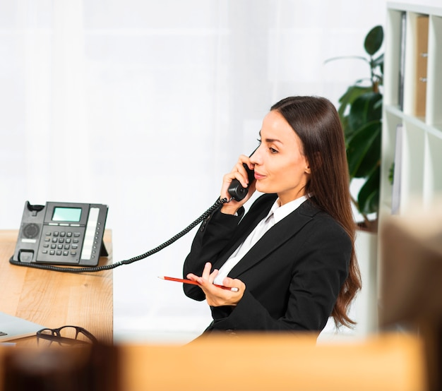 Beautiful young businesswoman shrugging while talking on telephone