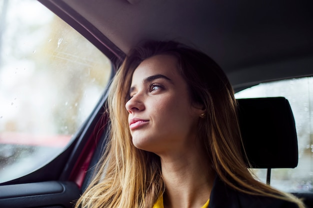 Beautiful young businesswoman sitting on back seat of a car and looking outside the window