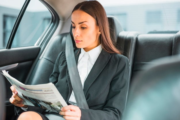 Beautiful young businesswoman traveling by car reading newspaper