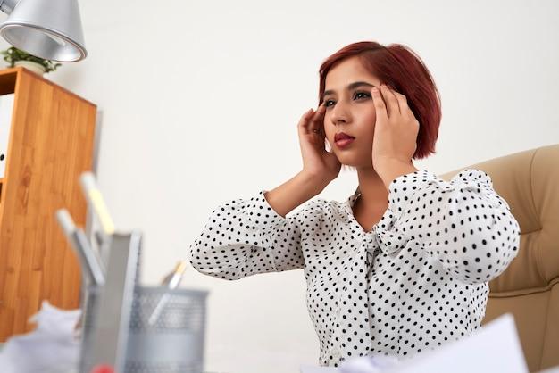 彼女が寺院に触れて見ている後、仕事に集中しようとしている美しい若い実業家...