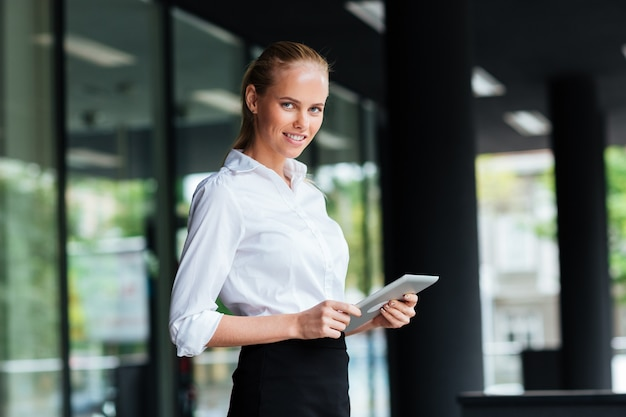 Beautiful young businesswoman using digital tablet while standing at the glass railing and looking at camera outdoors