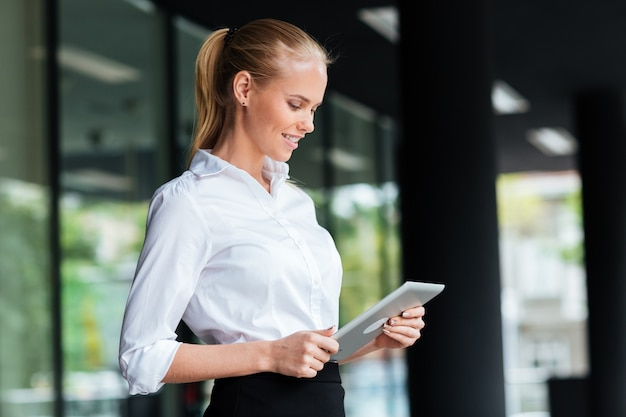 Beautiful young businesswoman using digital tablet while standing at the glass railing outdoors