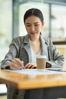 Beautiful young businesswoman using laptop and doing some paperwork