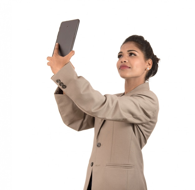 Beautiful young businesswoman using smartphone to take selfie photo isolated on white space