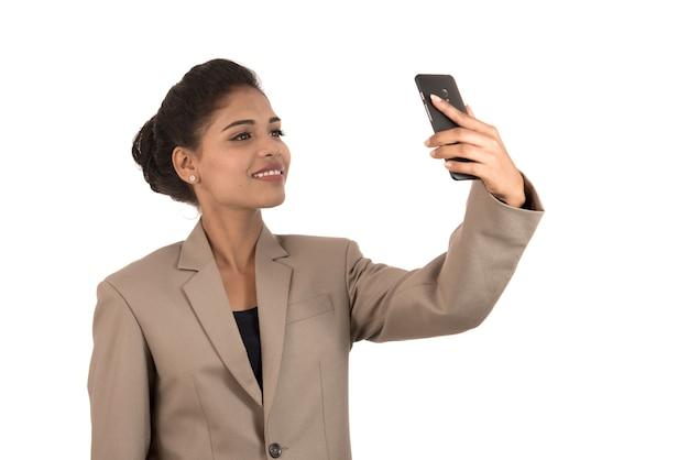 Красивая молодая деловая женщина с помощью смартфона, чтобы сделать селфи фото, изолированные на белом фоне