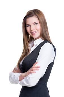 Bella giovane imprenditrice con le mani incrociate in piedi sul muro bianco.