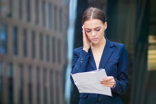 Beautiful young businesswoman with documents is suffering from headache