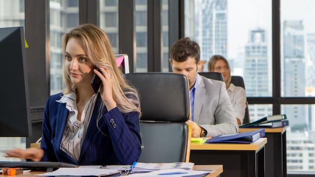 彼女のワークステーションで笑顔の電話でありながらラップトップに取り組んでいる美しい若い実業家