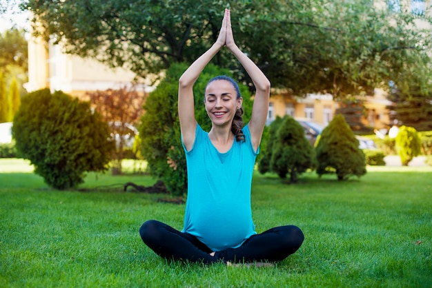 Beautiful young calm pregnant woman is sitting in the lotus position and meditating while practicing yoga in the park