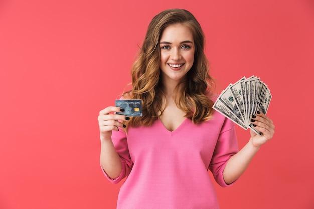 ピンクの壁に孤立して立っている美しい若いカジュアルなブロンドの女の子、プラスチックのクレジットカードとお金の紙幣を示しています