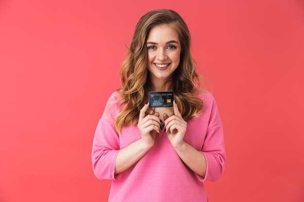 ピンクの壁に孤立して立っている美しい若いカジュアルなブロンドの女の子、プラスチックのクレジットカードを示しています