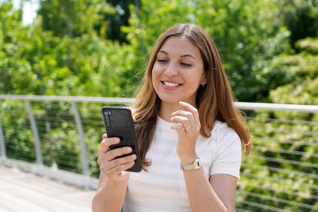 都市公園の携帯電話でテキストメッセージを送信する美しい若いカジュアルな女性
