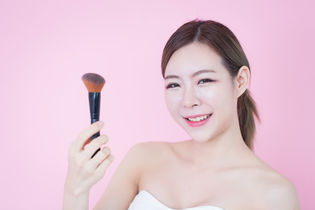 Beautiful young caucasian asian woman smile applying cosmetic brush powder natural makeup. cosmetology, skincare, cleaning face
