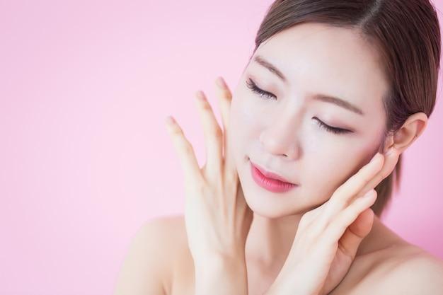 아름 다운 젊은 백인 아시아 여자는 그녀의 깨끗 하 고 신선한 피부 얼굴을 터치.