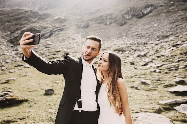Beautiful young caucasian bride and groom doing a selfie on the smartphone in front of mountains in their wedding day while groom is showing tongue.
