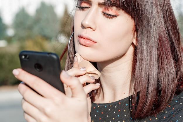 아름 다운 젊은 백인 갈색 머리 소녀는 거울로 전화를 사용하여 그녀의 얼굴에 기초를 둔다