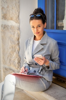 ドアの階段に座ってメモを取る美しい若い白人実業家