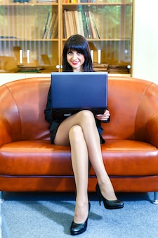 Beautiful young caucasian businesswoman working on laptop.