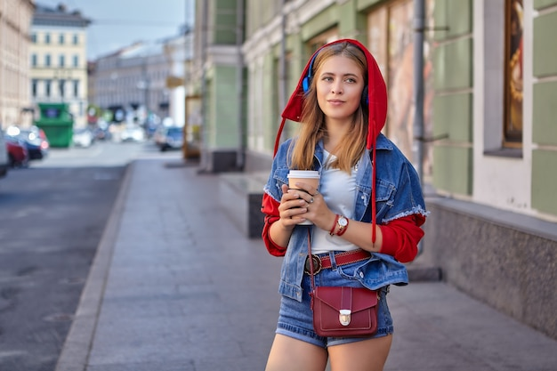 Beautiful young caucasian cheerful woman about 25 years old with blond hair and in red hoodie is walking in center of saint petersburg with paper cup of coffee during daytime.