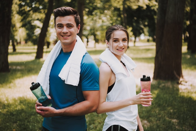 Beautiful young caucasian couple is posing after training.