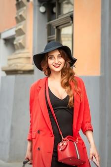 旧市街の通りに立っているスーツケースと赤いコートと黒い帽子の美しい若い白人のファッショナブルな女性