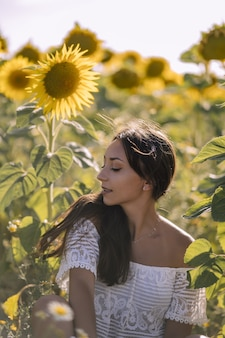 Beautiful young caucasian female posing in a field of sunflowers