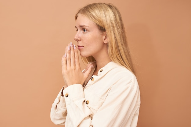 Beautiful young caucasian female pressing hands at her face in prayer her eyes full of hope. cute adorable blonde girl praying for wellness