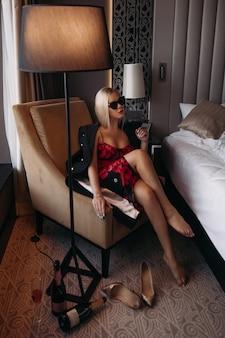 La bella giovane femmina caucasica con capelli biondi in occhiali da sole, vestito viola, vestito nero si siede nella sua stanza accogliente