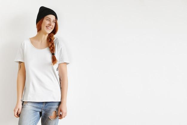 スタジオの壁に対して分離された三つ編みに立って生姜髪の美しい若い白人女性