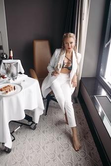 Bella giovane donna caucasica con lunghi capelli biondi, bel viso, orecchini luminosi in abito bianco