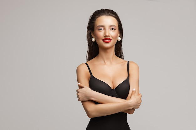 Beautiful young caucasian female with long dark hair, nice make up, red lips in black swimsuit smiles
