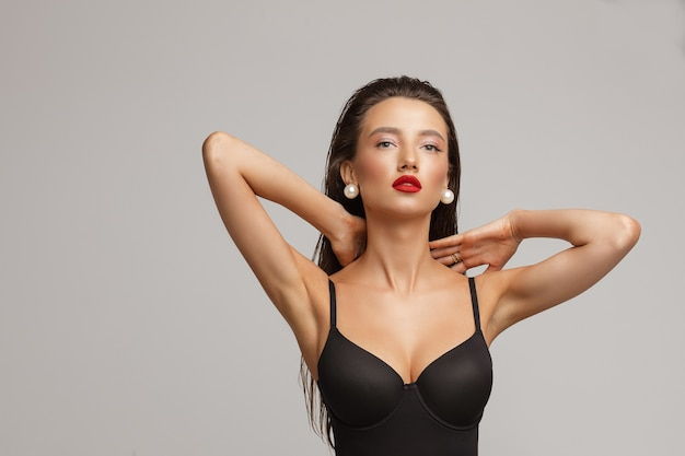 Beautiful young caucasian female with long dark hair, nice make up, red lips in black swimsuit