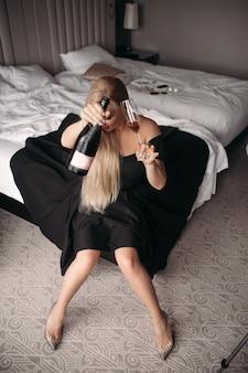 Bella giovane donna caucasica con lunghi capelli biondi, bel viso, trucco luminoso orecchini luminosi in abito nero lungo si siede sul grande letto bianco e beve vino