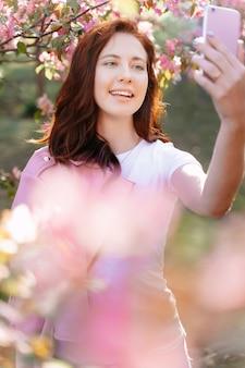 아름다운 백인 소녀 블로거가 분홍색 나무 근처에서 흰색 티셔츠를 입고 비디오를 쏜다
