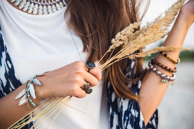 Beautiful young caucasian girl in clothes in the style of a boho with a lot of accessories of rings