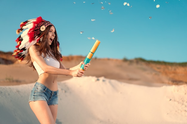 A beautiful young caucasian girl in a white top and denim shorts on her head is wearing an indian hat. roach is in the desert. shoots confetti crackers.