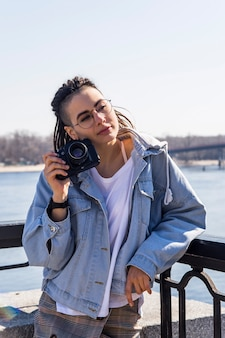 Beautiful young caucasian girl with dreadlocks holding a retro camera in her hands - photography as a hobby in traveling