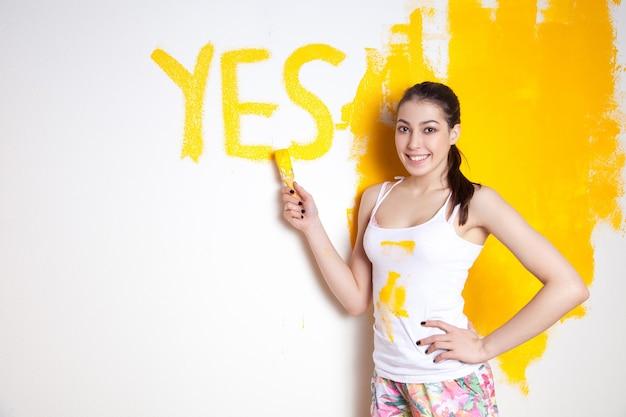Красивая молодая кавказская модель в цветных шортах и белой рубашке позирует, держа в руках аутригер, и пишет «да» на стене, красит стену и смотрит в камеру. студийный снимок.