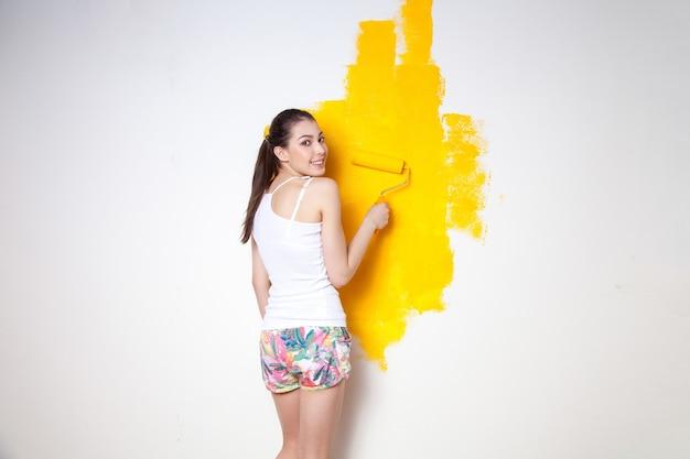 Красивая молодая кавказская модель в цветных шортах и белой рубашке позирует, держа в руках аутригер, красит стену и смотрит в камеру. студийный снимок.