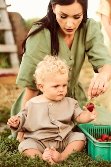 Beautiful young caucasian mother with her children in a linen dress with a basket of strawberries gathers a new crop and has fun with the children near the trailer