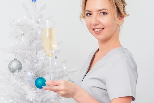 Красивая молодая кавказская улыбающаяся женщина-врач в защитных перчатках с бокалом шампанского стоит возле елки