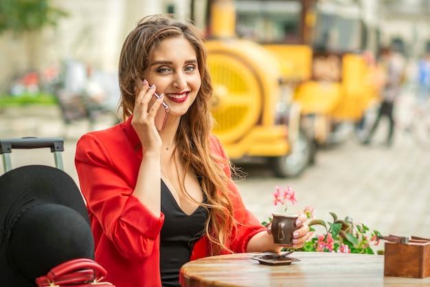 Красивая молодая кавказская туристка разговаривает по телефону, сидя за столом в уличном кафе в европейском городе