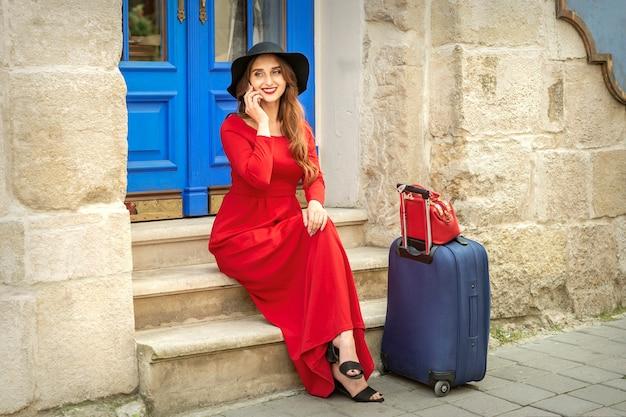 美しい若い白人観光客の女性が通りのドアの階段に座って電話で話します