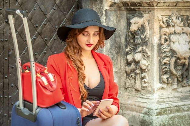 旧市街の通りに座ってスマートフォンでスーツケースを見て黒い帽子をかぶった美しい若い白人旅行の女性