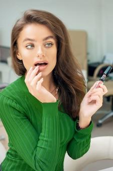 거울을보고 손가락으로 입술에 광택을 적용하는 아름 다운 젊은 백인 여자