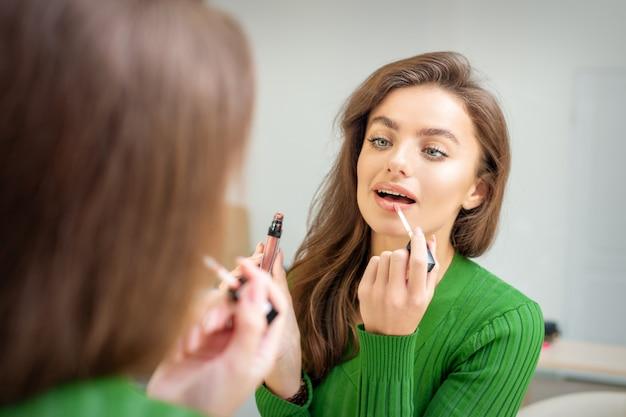 거울을보고 입술에 광택을 적용하는 아름 다운 젊은 백인 여자